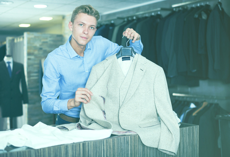 Adult male in shirt selling business clothes jacket in the store Stock Photo