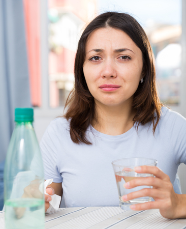 Upset girl suffering from troubles at table with bottled water  in home