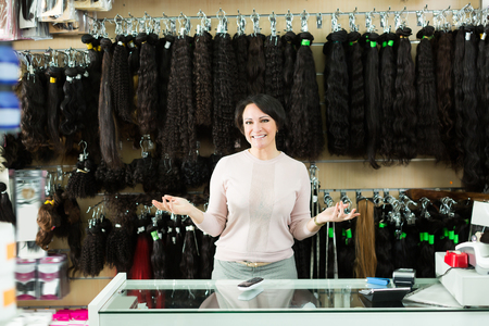 Positive female assistant selling natural hail ponytails, tresses and wigs