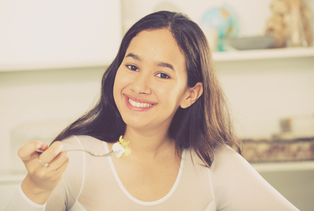 Glad young woman have lunch at home eating freshness salad Imagens