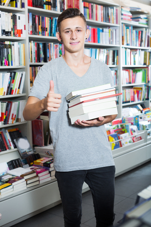 Positive young teenager holding pile of books in hands in store Stok Fotoğraf