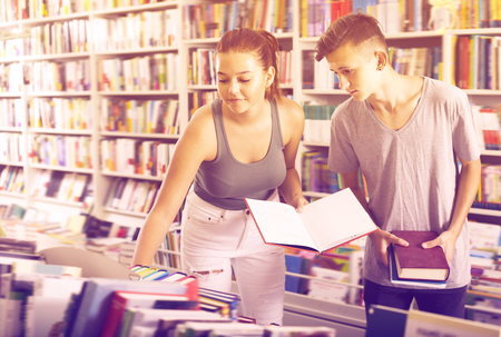Portrait of glad teenage girl and boy taking books together in shop