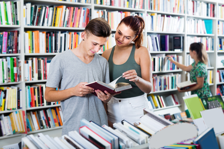 Two positive teenagers reading book together while choosing new literature in library