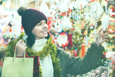 Smiling satisfied  pleasant teenage girl shopping at festive fair before Xmas Stock Photo