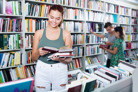 Smiling teenager girl reading book while looking new literature in shop