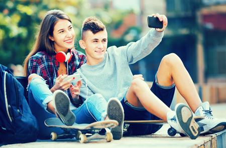 Smiling boy and girl teens posing at mobile phone for selfie