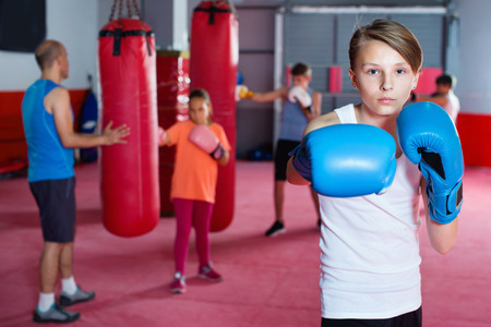 Portrait of young diligent serious positive boy boxer wearing gloves at boxing hall