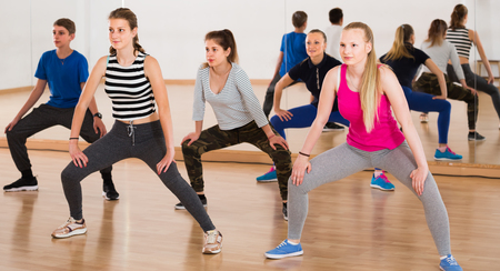 happy teenage boys and girls learning to dance in dance hall Stockfoto