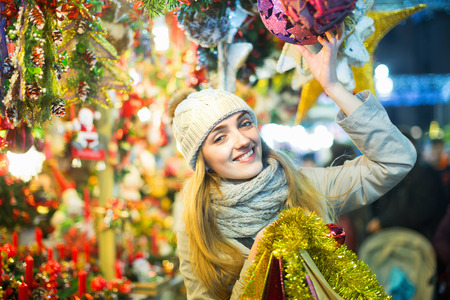 Happy Young cheerful woman at fair near counter with Christmas gifts in evening time