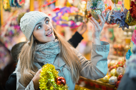 Young positive smiling woman at fair near counter with Christmas gifts in evening time