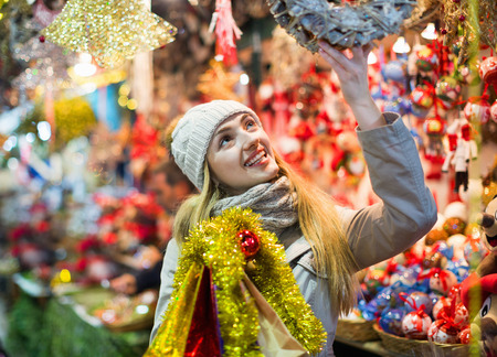 Beautiful smiling happy woman choosing Christmas decoration at market in evening time