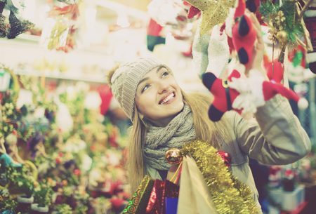 Beautiful happy woman choosing Christmas decoration at market in evening time