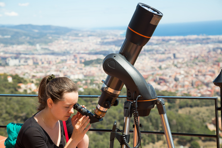 Portrait of woman looking in telescope on roof on summer day