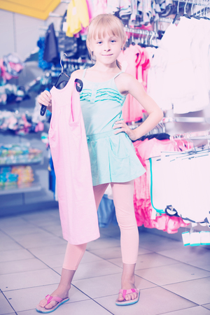 Portrait of happy swiss  girl choosing colored dress and wear in the shop