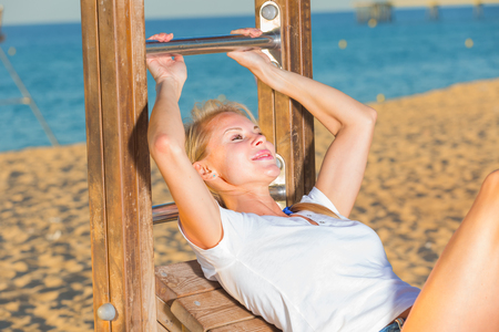 Smiling adult woman in white T-shirt is doing excercises on strenght on the beach. Imagens