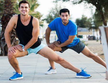 Portrait of two male friends who are stretching in the park near beach Imagens