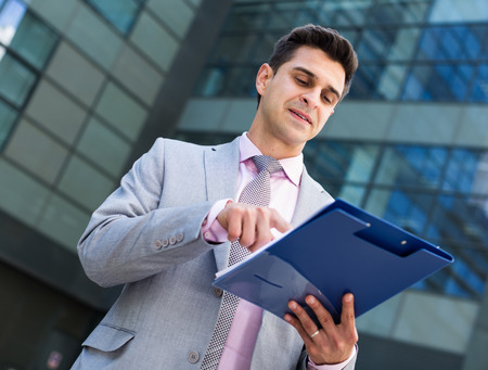 Businessman reading documents and pointing at clause of contract