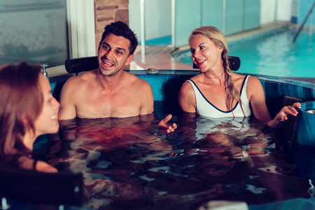 Man with two girlfriends are enjoying of relax together in pool in spa.
