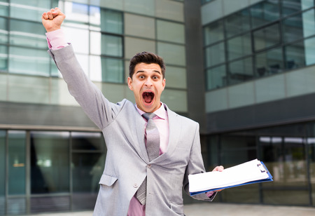 Happy enthusiastic business man celebrating success on background with large factory