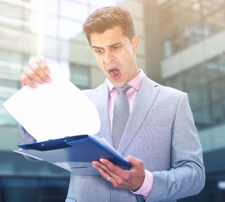 Businessman reading papers outdoor near large factory with shocked facial expression