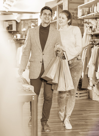 Young woman and man are walking satisfied with packadge after shopping in the clothes store. Stock Photo