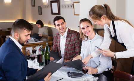 polite waitress bringing delicious salads to smiling people at cozy restaurant