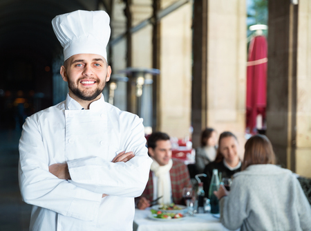 Confident glad cheerful  chef of restaurant posing with arms crossed
