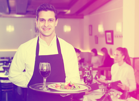Glad waiter holding tray at restaurant with customers his behind Фото со стока