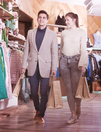 Smiling couple is satisfied of purchases and walking with package in the clothes store.