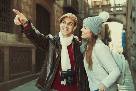 Happy adult travelers in hats and scarfs pointing finger on historical object