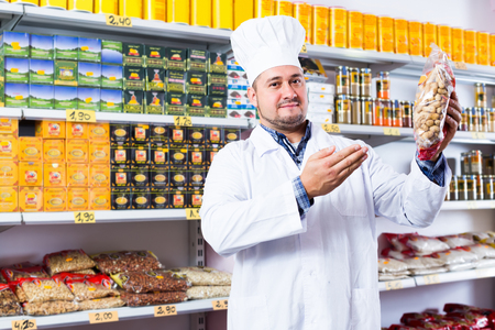 Seller posing with peanuts in local grocery store Stock Photo