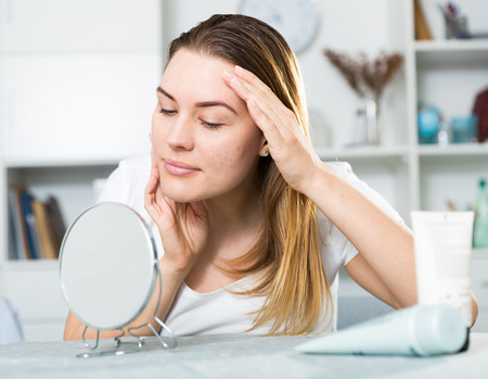 Cheerful woman is concentrared looking on her face in the mirror at the home. Stock Photo