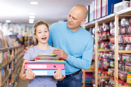 Smiling man with cute daughter visiting shop of stationery in search of school supplies