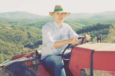 Portrait of adult man in straw hat sitting on tractor on background with vineyard