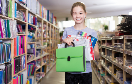 Portrait of cheerful preteen girl student  holding stack of school stationery in shop