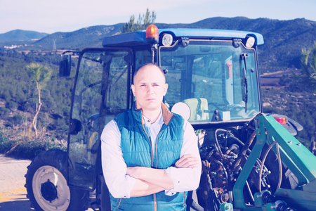 Portrait of attractive man standing near farm tractor in vineyard at sunny day Stock Photo