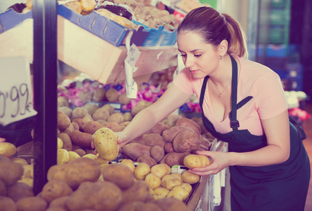 Young  smiling female seller putting fresh goods on shelves in greengrocery