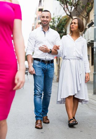 Young woman is resentmenting because her boyfriend was stared on other girl outdoors. Stock Photo