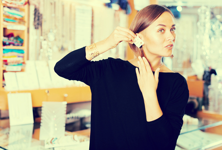 Portrait of positive female consumer trying earrings in the jewelry shop