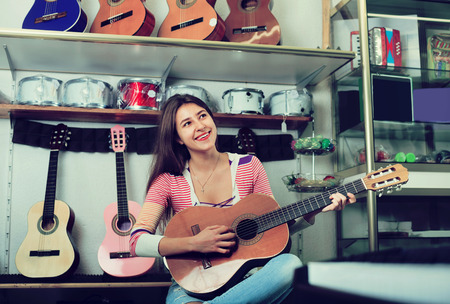Smiling teenage girl posing with classical guitar in shop