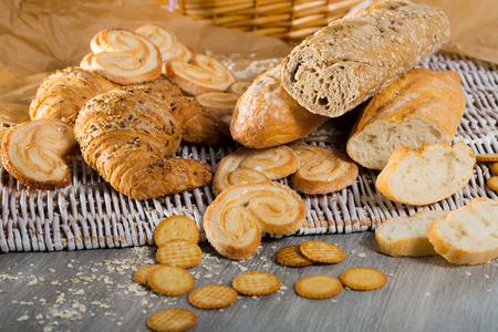 Assortment of fresh baked goods on wicker mat with basket on wooden background