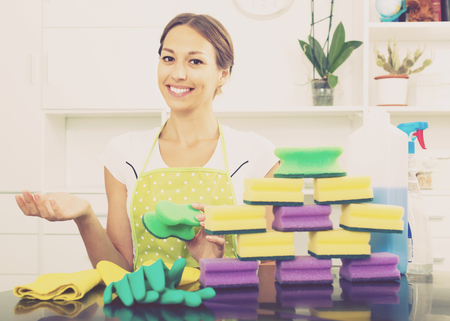 glad woman holding cleaning sponge in hands at home indoors Standard-Bild