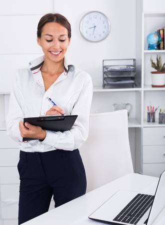 cheerful woman having clipboard in hands in company office indoors
