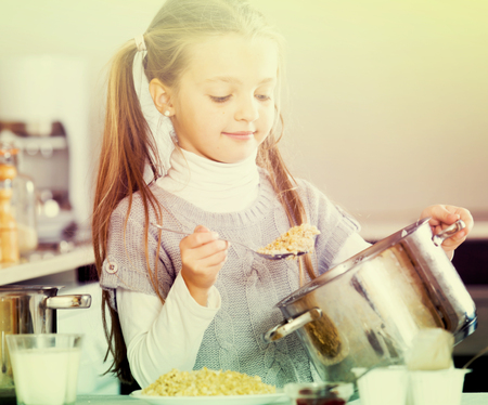 Small girl cooking oatmeal kasha in home kitchen and smiling 免版税图像