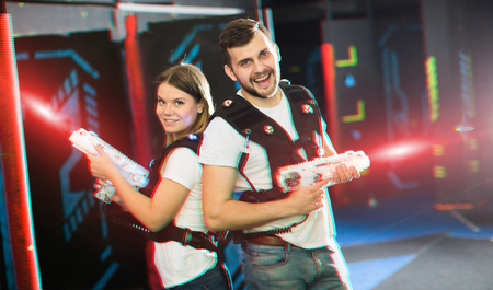 Couple standing back to back in colorful laser beams, holding guns during lasertag game in labyrinth