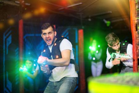 Portrait of guy in colored beams of laser guns during laser tag game on dark arena Reklamní fotografie