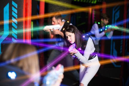 Porträt des Mädchens in den farbigen Strahlen der Laserpistolen während des Lasertagspiels auf dunkler Arena Standard-Bild