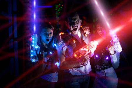 Gruppenporträt von jungen Leuten in bunten Strahlen von Laserpistolen, die Spaß auf Lasertag-Arena haben