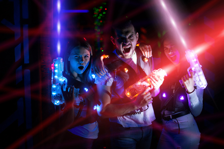 Retrato de grupo de jóvenes en coloridos rayos de pistolas láser divirtiéndose en la arena lasertag