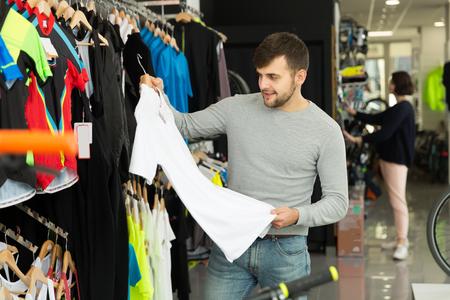 Ordinary man choosing sport shirt in bicycle shop 免版税图像 - 101617610